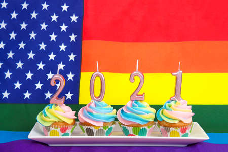 rainbow colored frosted vanilla cup cakes on a rectangular plate with 2021 New Year candles on top in pastel metallic pink. Gay Pride American flag in background.