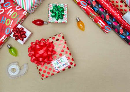 Top view flat lay of wrapped Christmas presents, ornaments, rolls of wrapping paper and roll of tape on brown wood paper background. Imagens