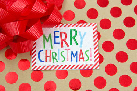 Top view flat lay close up of a colorful Merry Christmas label on a red polka dot on brown paper covered present with a red bow. Imagens