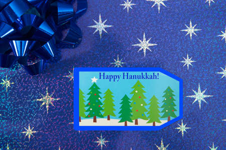 Top view flat lay close up view of Hanukkah present with blue bow and forest trees label. Happy Hanukkah text. Reflective blue paper with silver stars. Imagens
