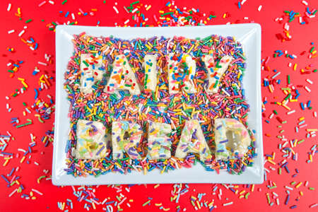 Fairy bread spelled with fairy bread on rectangular plate, bright red background with candy sprinkles spilled about. Fairy bread is commonly served at children's parties in Australia and New Zealand. Imagens