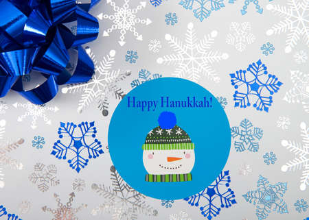 Top view flat lay close up view of Hanukkah present with blue bow and snowman label. Happy Hanukkah text. Blue snowflakes on white paper.