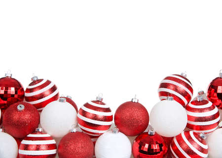 red white and striped Christmas tree ornaments piled decoratively in a row isolated on white background.
