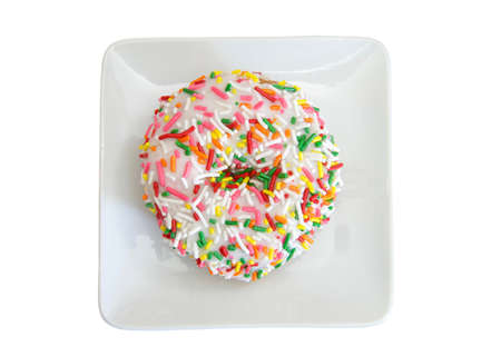 Top view flat lay of one vanilla cake donut with vanilla frosting covered in bright colorful candy sprinkles on a small square off white porcelain plate, isolated on white Imagens