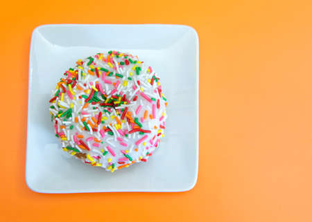 Top view flat lay of one vanilla cake donut with vanilla frosting covered in bright colorful candy sprinkles on a small square off white porcelain plate, on orange background.