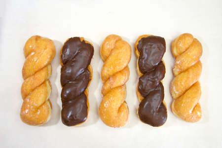 Top view flat lay of row of alternating glazed twist donut and chocolate covered glazed twist on parchment paper.