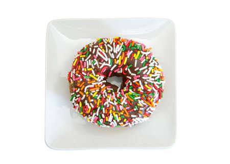 Top view flat lay of one vanilla cake donut with chocolate frosting covered in bright colorful candy sprinkles on a small square off white porcelain plate, isolated on white