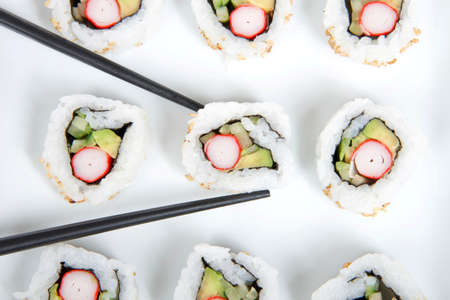 Close up Top view of California rolls sushi on a large square porcelain plate with black chop sticks.