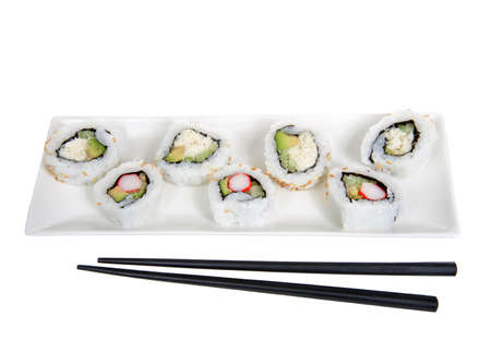 Close up top view of California rolls and crab roll sushi on a large rectangular porcelain plate with black chop sticks. Isolated on white Imagens