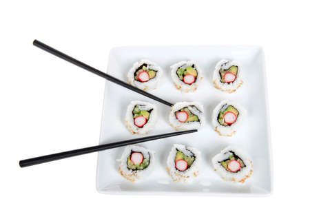 Close up top view of California rolls sushi on a large square porcelain plate with black chop sticks. Isolated on white.