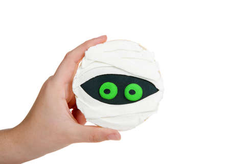 Young female hand holding a round sugar cookie decorated with homemade royal icing to create a Halloween theme mummy.  Isolated on white.