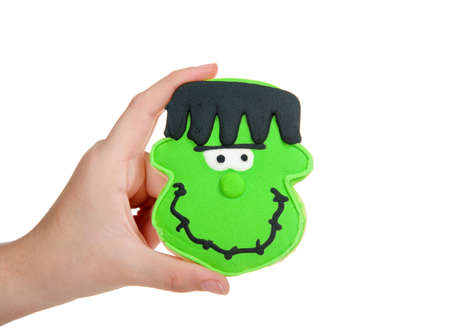 Young female hand holding a round sugar cookie decorated with homemade royal icing to create a Halloween theme Frankenstein type monster. Isolated on white.