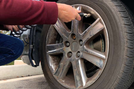 Close up of an older woman, female hands using automated air pump to inflate car tire with low pressure.