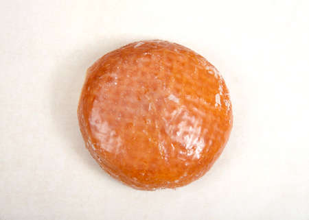 Flat lay top view of one glazed jelly donut on parchment paper. Banque d'images
