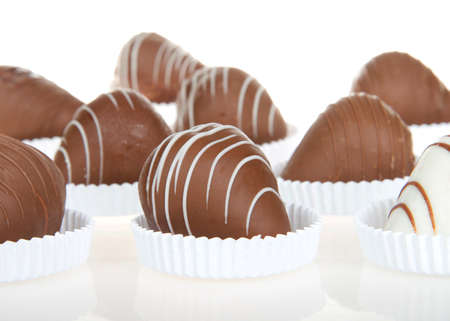 Close up on giant strawberries dipped in white and milk chocolate, drizzled with contrasting white and milk chocolate. sitting in shallow white paper pastry dishes on reflective surface