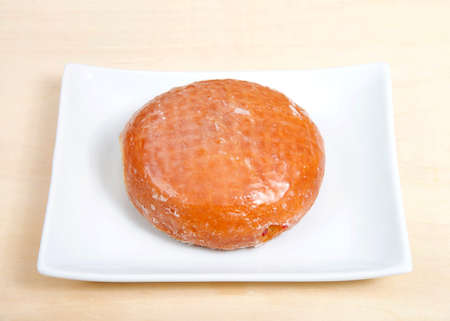 One round glazed jelly filled donut on a rectangular porcelain plate on a light wood table.