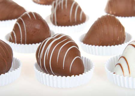 Close up on giant strawberries dipped completely in white and milk chocolate, drizzled with contrasting white and milk chocolate. sitting in shallow white paper pastry dishes on reflective surface Banque d'images