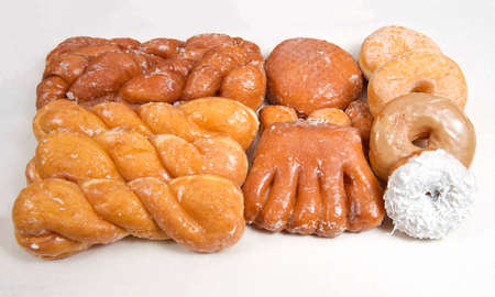 Variety of donuts arranged on parchment paper clustered together. Bear Claw, glazed twists, Cinnamon Twist, jelly filled, sugar coated, coconut covered.