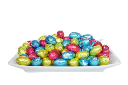 Close up of a rectangular porcelain plate filled with chocolate easter eggs covered with brightly colored foil wrappers