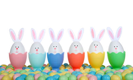 Row of Easter Eggs crafted into bunnies with felt ears, sitting in colorful egg cups with colorful candy coated chocolate egg candies, isolated on white background.
