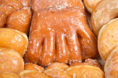 Close up on Variety of donuts arranged on parchment paper clustered together. Bear Claw in the center surrounded by glazed twists, Cinnamon Twist, jelly filled, sugar coated, coconut covered.