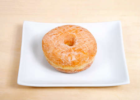 One round sugar coated donut on a rectangular porcelain plate on a light wood table.