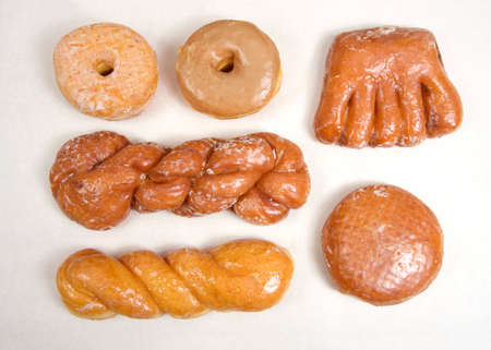 Flat lay top view of variety of specialty donuts. Glazed twists, cinnamon twist, jelly filled, bear claw, sugar coated and maple donuts.