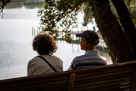 An Elderly Couple Enjoying a Sunrise Together by the Lagoon 版權商用圖片