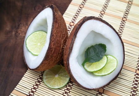 Cut coconut with a lime Stock Photo - 16549139