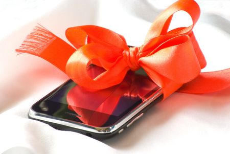 Cellular telephone in a gift lays on silk. photo
