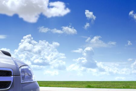 Car travelling over a beautiful green and blue landscape background. Stock Photo