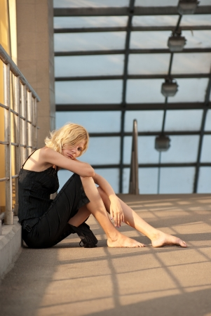 Portrait of a young female sitting on a floor of the bridge looking at the camera. photo