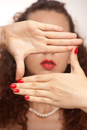 A model wearing thumb rings creates a frame around her face using only her hands. photo