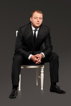 Businesman in black suit sitting on chair in dark room photo