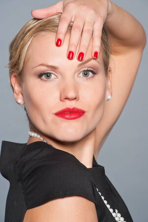 Closeup portrait of beautiful young caucasian women with retro glamour make-up and red bright manicure photo