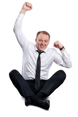 rejoices: Businessman rejoices as he sits cross-legged on the floor. Isolated on white background. Stock Photo