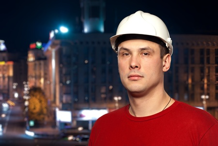 Young worker wearing a protective helmet standing against night city background.