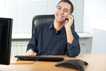 businessman talking: Young caucasian businessman talking on cell telephone and