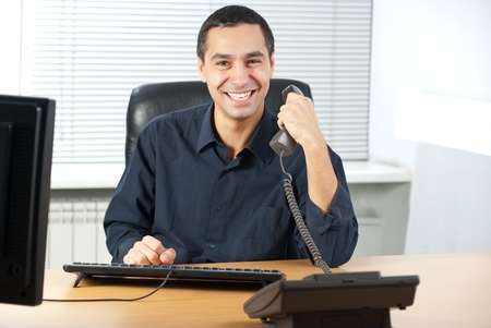 Young caucasian businessman talking on cell telephone and  photo