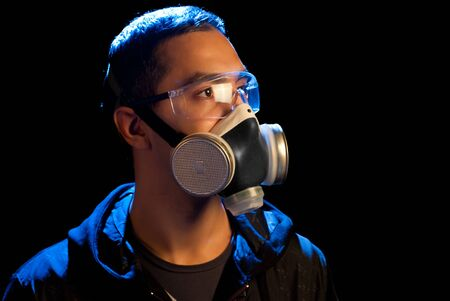 A man in a respirator and glasses. Isolated on black. Stock Photo