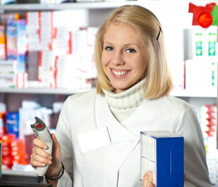 Cheerful pharmacist with barcode reader in hand. photo