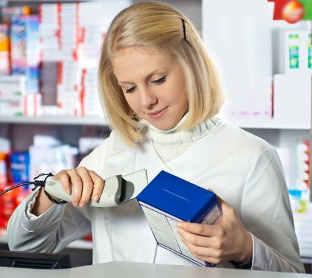 Pharmacist scanning medicine with barcode reader