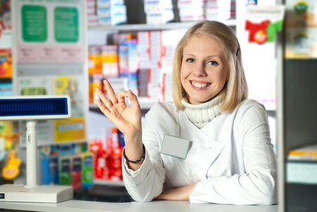 Shot of woman pharmacist give OK sign and smiling to camera. Stock Photo