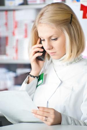 Pharmacist reading prescription at pharmacy and talking on phone  Stock Photo