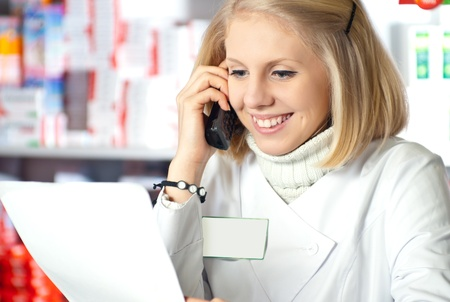 Pharmacist reading prescription at pharmacy and talking on phone Stock Photo - 9227107