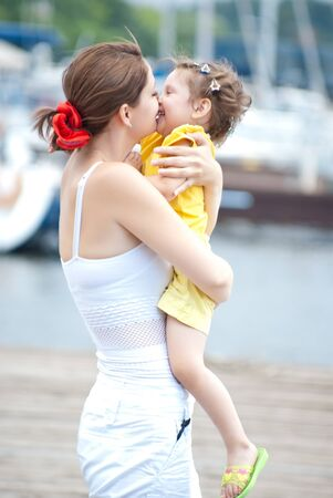 yacht club: Mom embraces the daughter on a pier in yacht club Stock Photo