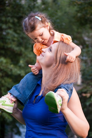 Happy young girl  sitting on her mothers shoulders photo
