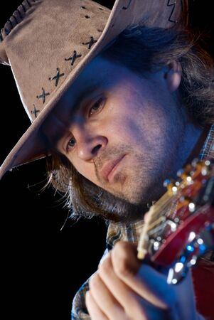 Guitarist. Closeup shoot of man wearing cowboy hat playing on a acoustic guitar. Isolated on black background. photo