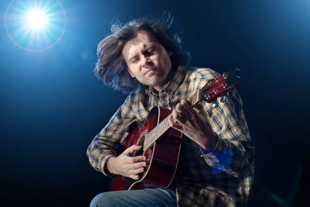Guitar playing. Man with long hair playing acoustic six-string guitar. Isolated on black background. Stock Photo