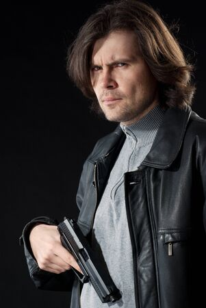 Man in leather wear holding gun.  photo